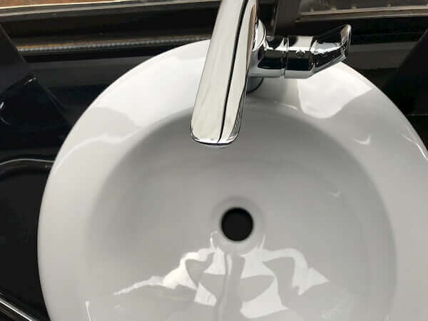 White ceramic bathroom sink bowl with stainless steel faucet